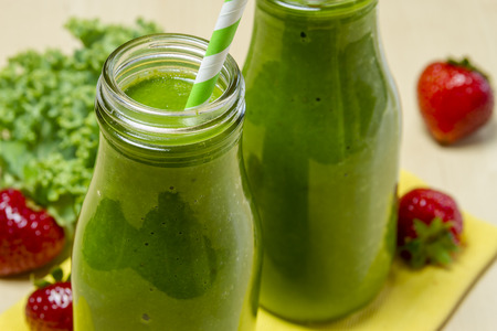 Close up of healthy green juice smoothie in glass bottle sitting on yellow napkin with fresh strawberries and kale