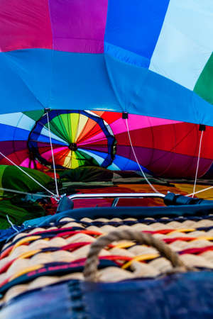 inflation basket: View of inside of multi-colored hot air balloon and basket during inflation Stock Photo