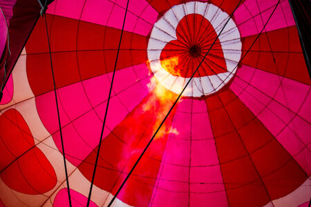View of top of heart hot air balloon during inflation with flame from basket
