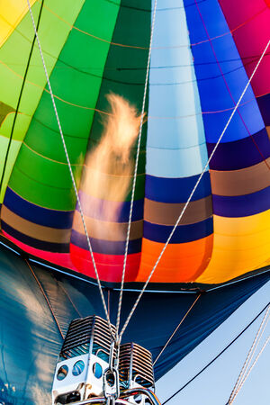 inflation basket: Vista del interior del multicolor globo de aire caliente y la canasta durante el inflado con la llama