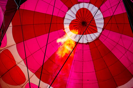 inflation basket: View of top of heart hot air balloon during inflation with flame from basket