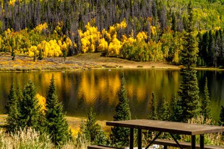 changing color: Cerca de la mesa de picnic en la orilla del lago de la monta�a en la c�lida tarde de oto�o con �rboles de colores brillantes cambiantes de colores que refleja en la superficie del lago
