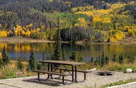 changing color: �rea de picnic en la orilla del lago de la monta�a en la c�lida tarde de oto�o con �rboles de colores brillantes cambiantes colores que refleja en la superficie del agua Foto de archivo