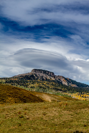 lenticular: Large Lenticular cloud positioned over flat top mesa mountain with changing fall colors on autumn afternoon