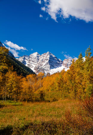 Maroon Bells mountain peaks covered with freshly fallen snow near Aspen Colorado on sunny fall morning