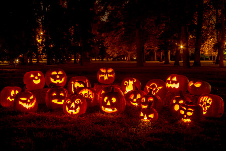 halloween decoration: Group of candle lit carved Halloween pumpkins in park on fall evening Stock Photo