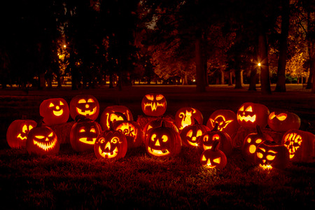 Group of candle lit carved Halloween pumpkins in park on fall evening Stock Photo
