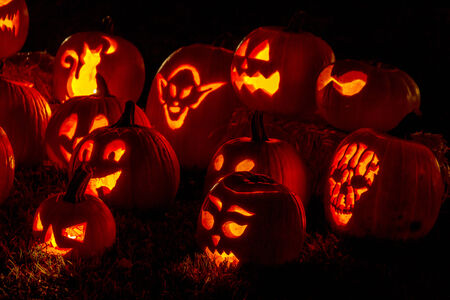 Close up of carved Halloween pumpkins lit with candles sitting on fallen leaves and hay bales