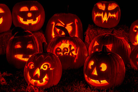 flickering: Close up of carved Halloween pumpkins lit with candles sitting on fallen leaves and hay bales