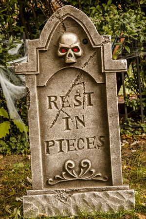 Scary Halloween skeleton gravestone with rest in pieces message on front