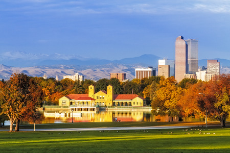 Denver Colorado skyline from City Park with City Park Boathouse and Rocky Mountains in background on autumn morning