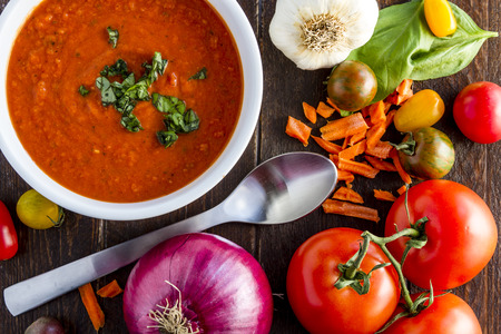 Homemade tomato and basil soup in white bowl with spoon surrounded by fresh vegetable ingredients Stockfoto