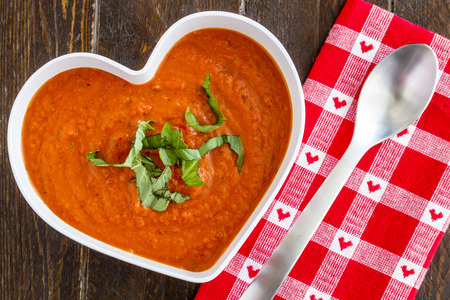 shaped: Homemade tomato and basil soup in white heart shaped bowl with spoon and red heart napkin