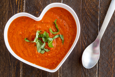 vegetable soup: Homemade tomato and basil soup in white heart shaped bowl with spoon, whole wheat crackers, heirloom tomatoes and red heart napkin