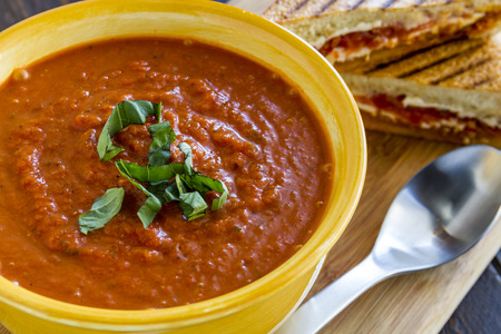 Homemade tomato and basil soup in yellow round bowl with spoon and grilled cheese panini sandwich sitting on wooden cutting board photo