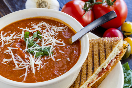 Homemade tomato and basil soup sprinkled with parmesan cheese in white round bowl with spoon and grilled cheese panini sandwich photo