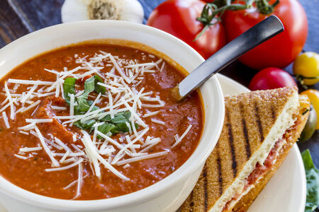 Homemade tomato and basil soup sprinkled with parmesan cheese in white round bowl with spoon and grilled cheese panini sandwich Banco de Imagens