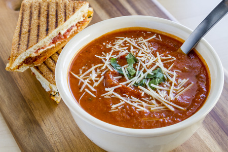 Homemade tomato and basil soup sprinkled with parmesan cheese in white round bowl sitting on wooden cutting board with grilled cheese panini sandwhich photo