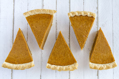 feast: 5 slices of homemade pumpkin pie in row sitting on white wooden table Stock Photo