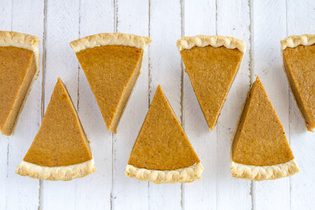 7 slices of homemade pumpkin pie in row sitting on white wooden table Reklamní fotografie