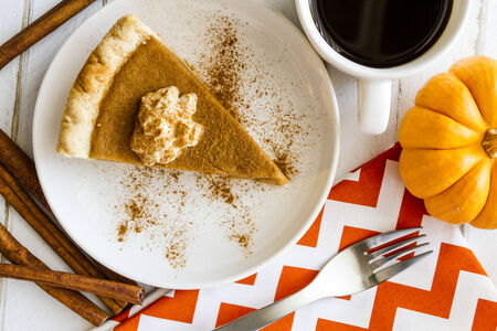 feast: Slice of homemade pumpkin pie with whipped cream sprinkled with cinnamon sitting on white plate with cup of coffee, small pumpkin and cinnamon sticks Stock Photo