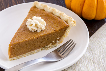 Single slice of homemade pumpkin pie with dollop of whipped cream sitting on white plate with fork photo
