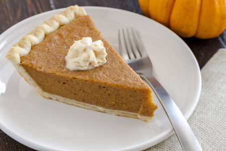 dollop: Single slice of homemade pumpkin pie with dollop of whipped cream sitting on white plate with fork