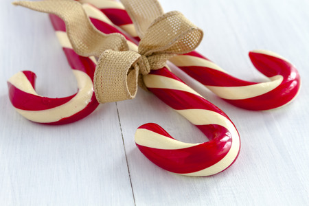 3 large red and white striped candy canes tied with brown burlap ribbon sitting on white wooden table Stock Photo