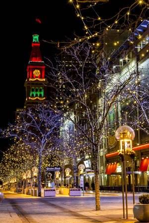 DENVER COLORADO  U.S.A. - December 7, 2014: Holiday light display along Denvers 16th Street Mall with historic landmark the Daniel Fisher Tower in distance with red and green lights on December 8, 2014 in Denver, Colorado