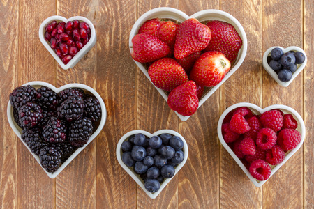 purple hearts: Fresh organic pomegranate seeds, blackberries, raspberries, blueberries and strawberries arranged in heart shapes on wooden table