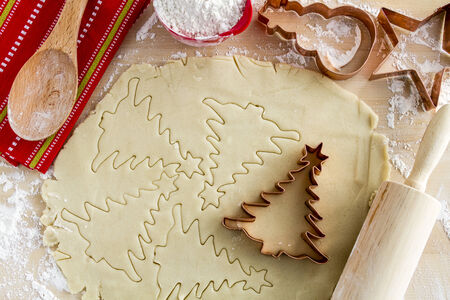 Copper cookie cutters cutting out holiday sugar cookies with wooden rolling pin and spoon and colorful kitchen towel photo
