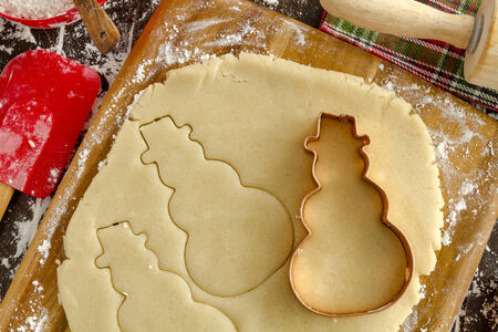 wood cutter: Close up of snowman copper cookie cutter cutting out holiday sugar cookies with wooden rolling pin and red spatula sitting on dark wood table Stock Photo