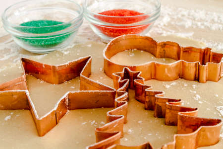 Close up of star, snowman and Christmas tree copper cookie cutters cutting out holiday sugar cookies with red and green sugar sprinkles photo