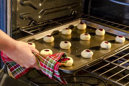 odcisk kciuka: Pan z malin ciasteczek Thumbprint siedzących na blasze umieszczeniem w piecu upiec