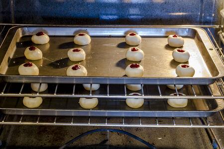 odcisk kciuka: 2 garnki z malin Thumbprint ciasteczka ułożone na półkach w piecu do pieczenia
