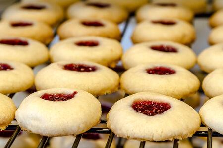 odcisk kciuka: Wiersze z malin Cookies odcisk palca chłodzenia na drut pieczenia szafie siedzi na blacie Zdjęcie Seryjne