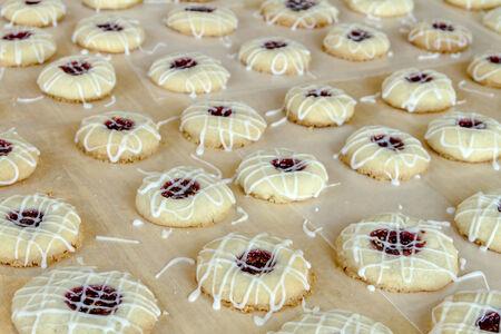 empreinte du pouce: Des rang�es de biscuits framboise thumbprint avec gla�age de sucre en poudre bruine assis sur un papier cir�