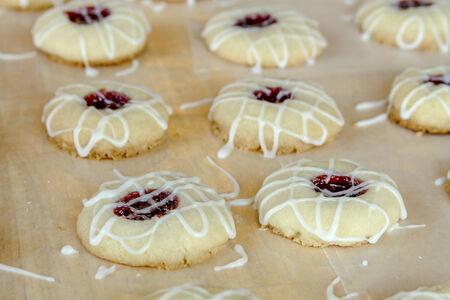 odcisk kciuka: Rzędy ciasteczka malinowy odcisk palca z cukier puder lukier mżawka siedzi na papierze wosku Zdjęcie Seryjne