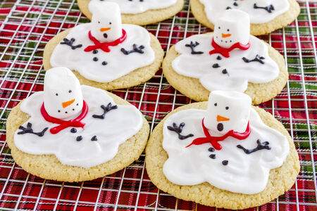 Melting snowman sugar cookies sitting on wire baking rack with colorful holiday napkin photo
