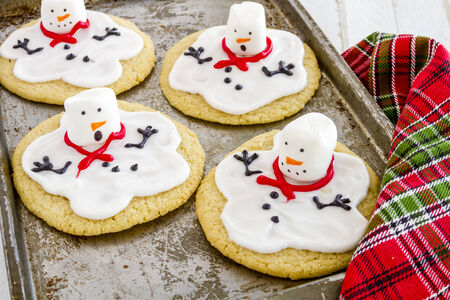 Melting snowman sugar cookies sitting on metal baking sheet with colorful holiday napkin photo