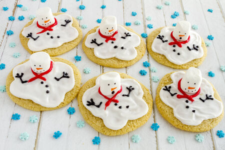 Melting snowman sugar cookies sitting white wooden table top with blue snowflake sprinkles