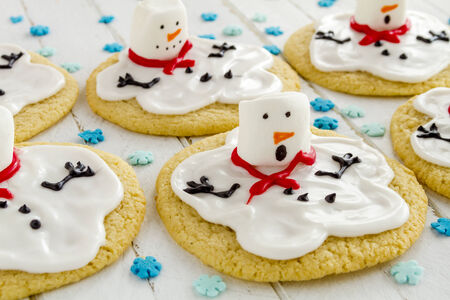 Close up of melting snowman sugar cookies sitting white wooden table top with blue snowflake sprinkles photo