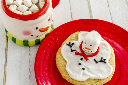 snowman wood: Melting snowman sugar cookie sitting on red plate with snowman mug filled with hot chocolate and marshmallows