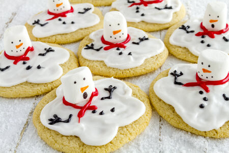 Melting snowman sugar cookies sitting on white wooden table with sparkling sugar snow photo