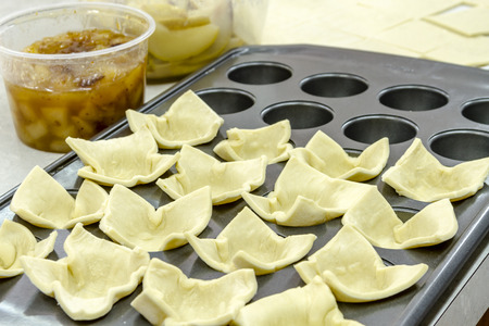 Puff pastry dough sitting in baking pan with small cups Stock Photo