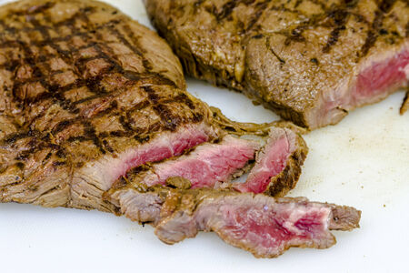 Rare top sirloin steaks with grill marks and several cut slices sitting on white cutting board