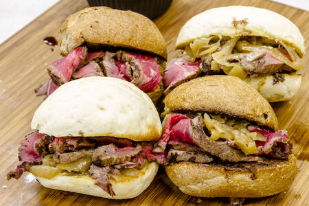 Finished top sirloin steak and grilled onion slider sandwiches sitting on wooden cutting board Stock Photo