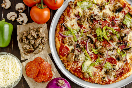Fresh baked thin crust supreme pizza with fresh mushrooms, onions, green peppers, tomatoes, pepperoni, sausage and cheese Stockfoto