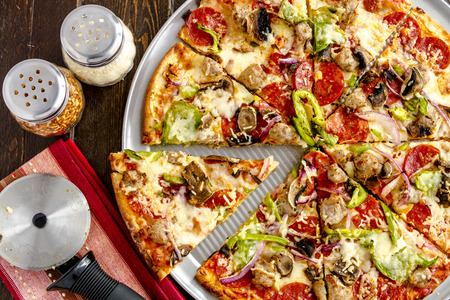 Sliced fresh baked thin crust supreme pizza sitting on metal pan with shakers of red pepper flakes and parmesan cheese with striped napkin and pizza cutter