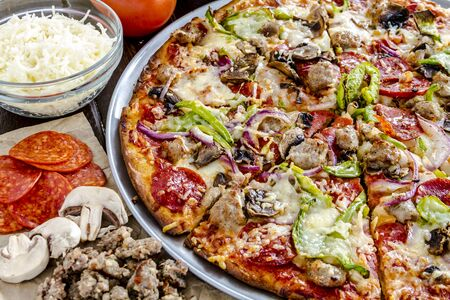 Close up of fresh baked thin crust supreme pizza surrounded by sausage, pepperoni, mushrooms, cheese and tomato ingredients Stock Photo